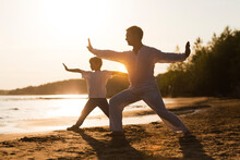 Family  Dad And Little Son Practice Tai Chi Chuan In The Summer On The Beach. Solo Outdoor Activities. Social Distancing. Family Exercising  Together. Simple Living