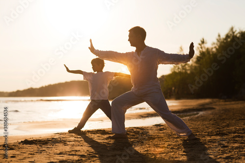 Foto Family  dad and little son practice Tai Chi Chuan in the summer on the beach