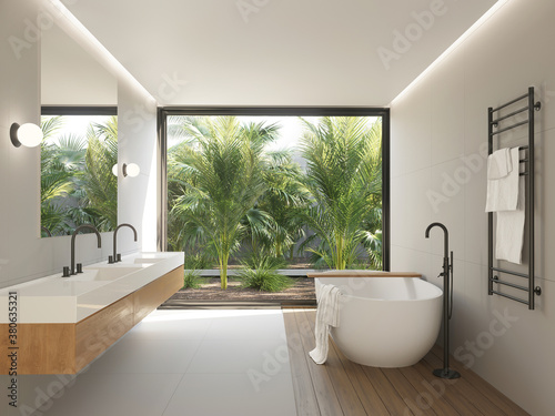 Beige modern bathroom with a view to a palm trees garden a bathtub