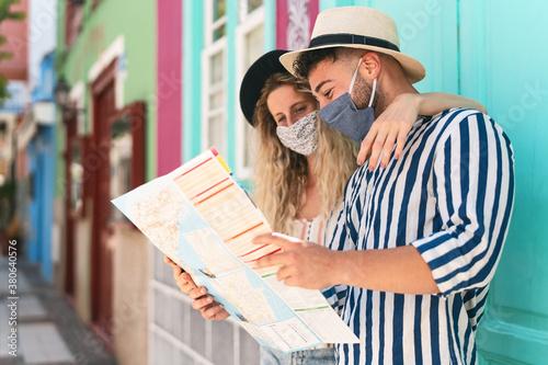 Fotografie, Obraz Young couple wearing face mask and holding travel map - Travelers people enjoyin