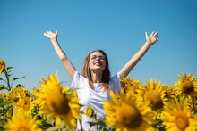 Young Woman In A White T-shirt And Glasses With Raised Up Hands On A Sunflower Field On A Summer Sunny Day