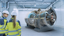 Industry 4.0: Two Engineers Standing, Talking In Factory Workshop With Augmented Reality 3D Turbine Engine, Analysing Components, Fuel Use Efficiency. VFX Special Visual Effects And Graphics