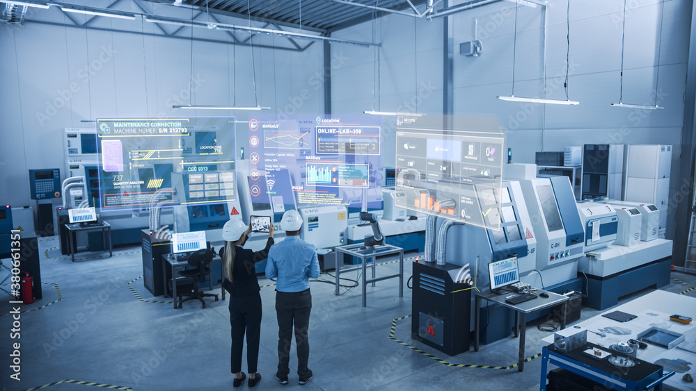 Fototapeta Industry 4.0 Factory: Two Engineers Uses Digital Tablet Computer with Augmented Reality Software to Connect with High-Tech Machinery, Robot Arm and Visualize Maintenance and Diagnostics of Equipment