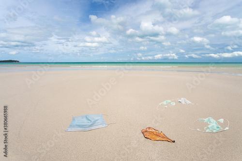 Fototapeta Garbage from used medical masks on the beach. obraz