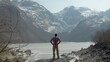 A Hiker Enjoys an Amazing View of a Frozen Lake and Bondhusdalen Glacier in the Mountains of Norway