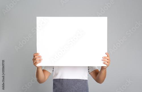 Man holding white blank poster on grey background Wallpaper Mural