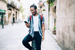 Smiling african american trendy dressed hipster guy in eyewear recreating outdoors using smartphone and sound application for enjoy music, positive dark skinned male listening audiobook on street