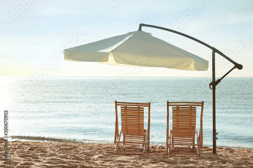 Obraz Wooden deck chairs and outdoor umbrella on sandy beach. Summer vacation - fototapety do salonu