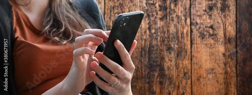 Canvas Print Junge Frau mit Handy beim Chaten vor einer vintage Holzwand