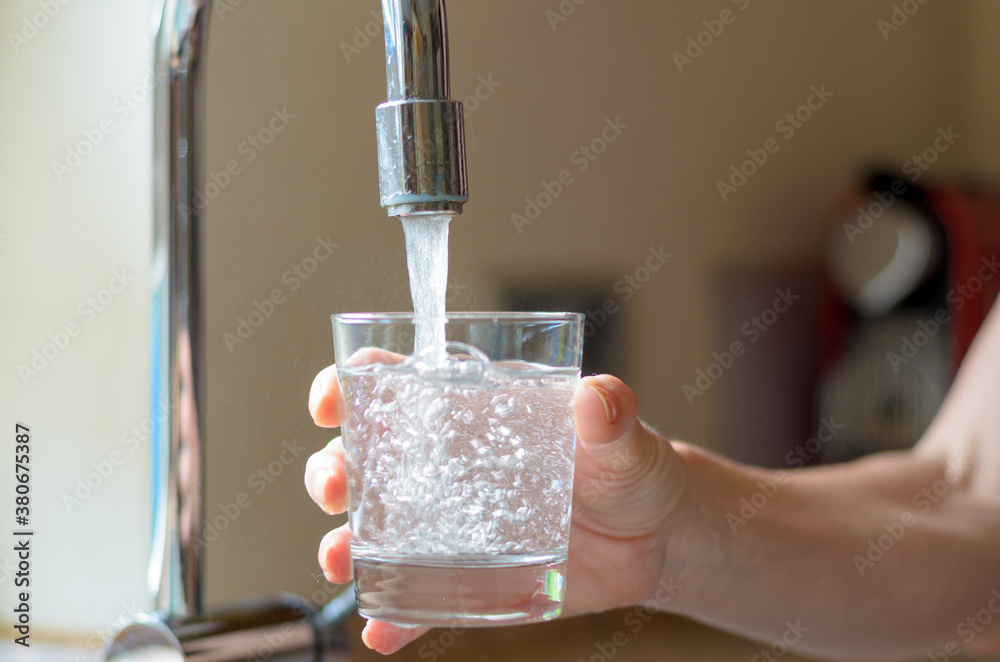 Fototapeta Woman filling a glass of water from a tap