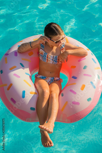 Fototapeta cute young girl playing in a swimming pool with her inflatable donuts obraz