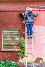Female Graffiti Artist Writing...