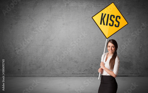 Fotografie, Obraz Young business person holding road sign with KISS inscription, new rules concept