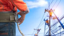 Midsection Of Electrician Lineman Wearing Safety Belt With Blurred Background Of Electrical Workers Team Are Working On Power Poles In Public Area