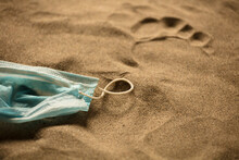 Waste During COVID-19. Discarded To Single-use Coronavirus Face Masks. Pollution Of The Environment, On The Beach, Man Footprint In The Sand