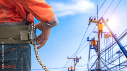 Midsection of electrician lineman wearing safety belt with blurred background of Canvas Print