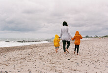 Mother And Children Walking Barefoot On Beach
