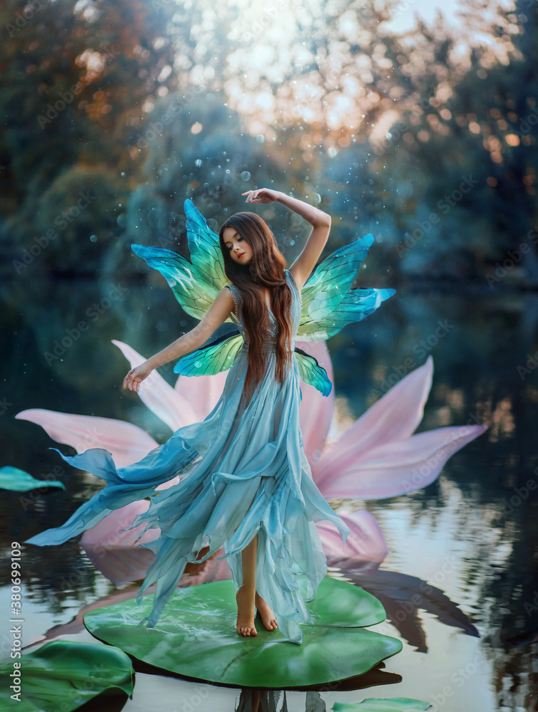 Fototapeta Beautiful young fantasy woman in the image of a river fairy dances on a water lily flower. A long silk dress flies in the wind, butterfly wings glisten. Background evening dark nature, blue lake.