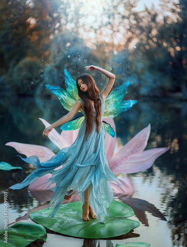 Fototapeta premium Beautiful young fantasy woman in the image of a river fairy dances on a water lily flower. A long silk dress flies in the wind, butterfly wings glisten. Background evening dark nature, blue lake.