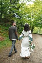 Newlyweds Walking Among Mounta...