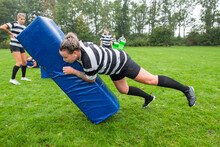 A Female Rugby Player Is Tackling The Tackle Bag Hard During Pra