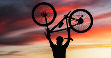 Silhouette Of Mountain Biker Lifting His Bike As A Symbol Of Victory During A Sunset. Personal Motivation