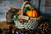 Autumn Composition With A Basket Of Pumpking And A Thank You Note, Surrounded By Dried Sunflowers, Chesnuts And Pinecone On A Wooden Background