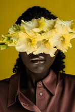 Closeup Portrait Of A Charming African Girl Covering Her Eyes With A Yellow Flower Of Gladiolus On The Yellow Background