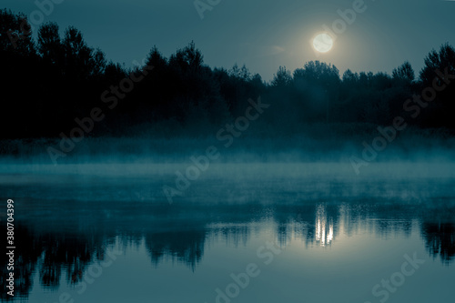 Fototapeta Night mystical scenery. Full moon over the foggy river and its reflection in the still water. obraz