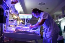 Nurse Touching Fragile Newborn...
