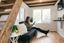 Home: Woman On Couch Reading Digital Tablet
