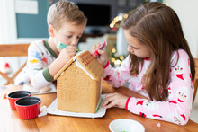 Brother And Sister Decorating A Gingerbread House For The Holidays