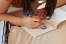 Crop Teenager Drawing On Bed