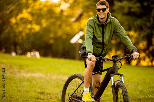 Young man riding ebike in the park Fototapeta