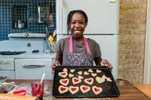 Smiling African American Girl With Tray Of Valentine's Day Cooki