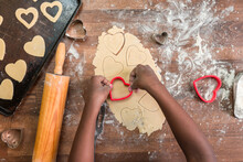 Black Girl's Hands Cutting Heart Shaped Cookies Out Of Rolled Do
