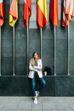Young Trendy Girl Sitting Besides International Flags