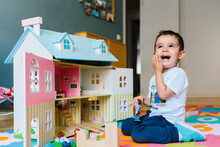 Kid Playing With Doll House At Home