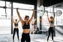 Women Exercising With Barbells...