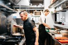 Two Cooks Preparing Paella In ...