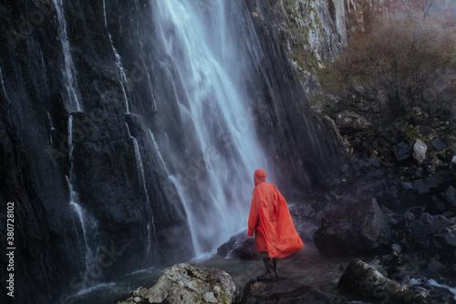Orange man looking at a waterfall - 380728102