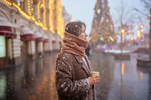 Portrait Of A Girl With A Cup Of Takeaway Coffee During A Snowfall On Red Square In Moscow