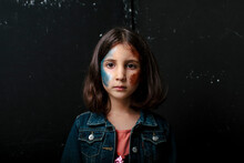 Kid With Glitter On Her Face Looking Pensive