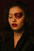 Closeup Portrait Of An Asian Girl In The Dark With Heart-shaped Red Glitters Around Her Eye And Red Lipstick In Black Silk Dress