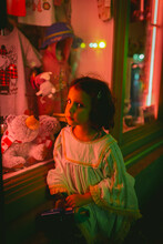 Girl Sitting By A Neon Lighted...