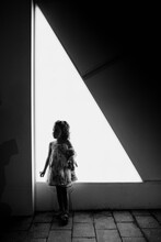 Kid In Backlight Over White Triangle Shaped Lighted Background