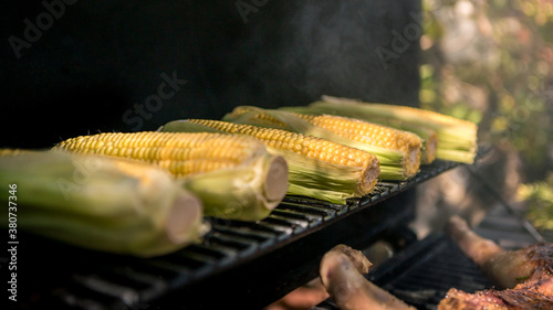 Chef cooking BBQ with a corn on the cob on grilled Fototapet