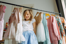 Girl Choosing Dresses Standing By A Clothing Rack
