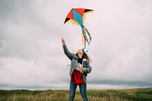 Young Woman And Colorful Flying Kite In The Air