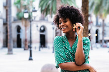 Happy Young African American Female With Curly Hair And Stylish Earrings Wearing Trendy Green Polka Dot Blouse With Eyes Closed While Standing Against Blurred Urban Background